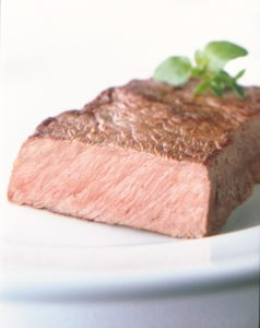Medium well steak cut in half on white plate