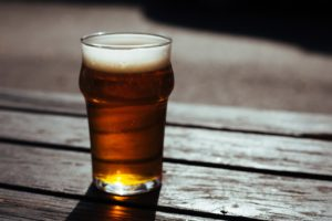 Glass of beer on wooden table. Ambient Shot.